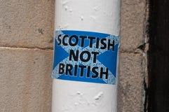 Autocollant non britannique d'écossais sur un poteau blanc dans une rue écossaise Image libre de droits