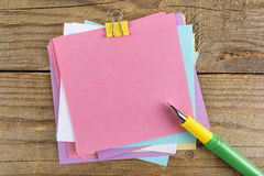 Autocollants colorés autour de carnet sur la vieille table en bois Photographie stock