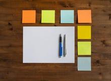 Autocollants colorés, feuille de papier et deux stylos Images stock