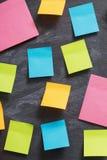 autocollants de papier de couleur sur le fond noir Photographie stock libre de droits