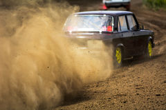 Autocross on a dusty road. Cars in the competition on a winding road stock image
