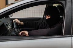 Autodieb, der ein gestohlenes Auto fährt Lizenzfreie Stockfotografie
