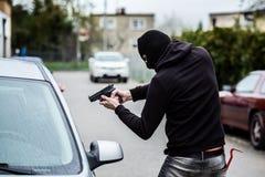 Autodieb, der ein Gewehr auf den Fahrer zeigt Stockfotos