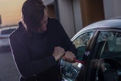 Autodief in zwarte balaclava die in auto proberen te breken royalty-vrije stock foto