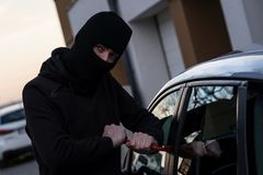 Autodief in zwarte balaclava die in auto proberen te breken royalty-vrije stock fotografie