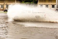 Autodurch Hochwasser auf der Straße schnell fahren Lizenzfreie Stockfotografie