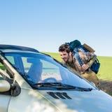 Autoestop consiguiendo a elevación la mujer joven en coche Foto de archivo