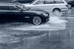 Autofahren auf überschwemmte Straße mit Spritzwasser nach schwerem rai Lizenzfreie Stockbilder