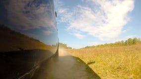 Autofahren auf dem Gebiet, ein Auto hebt Staub auf stock video