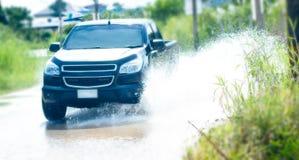Autofahren durch den Hochwasser auf der Straße lizenzfreie stockfotos
