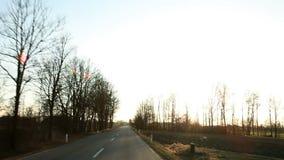 Autofahren hinunter die Straße in einem Sonnenuntergang stock video footage