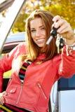 Autofahrerfrau, die Neuwagenschlüssel und -auto zeigt. Stockbilder