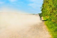 Autofahrt auf eine staubige Straße in einer staubigen Wolke lizenzfreies stockbild
