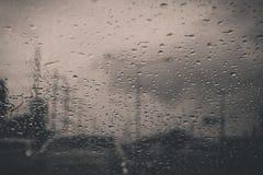 Autofenster mit Regentropfen auf Glas oder der Windschutzscheibe, unscharfer Verkehr am regnerischen Tag in der Stadt stockbild