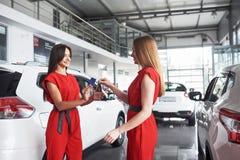 Autogeschäft-, Autoverkaufs-, Abkommen-, Gesten- und Leutekonzept - nah oben vom Händler, der dem neuen Eigentümer in der Automob Stockfoto
