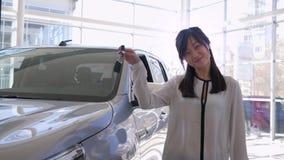 Autogeschäft, Porträt des lächelnden Verkäuferinklapsautos mit Vergnügen und Showschlüssel zum neuen Automobil für Verkauf in den stock footage