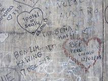 Autografer på en grå gammal vägg, bakgrundstextur Fotografering för Bildbyråer