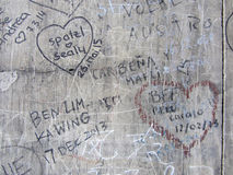 Autographs on a gray old wall, background texture Stock Image