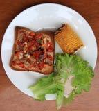 Autoguidez la pizza faite sur le pain coupé en tranches par place avec le maïs et la laitue grillés dans le plat rond blanc sur l photographie stock libre de droits