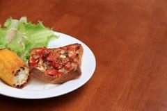 Autoguidez la pizza faite sur le pain coupé en tranches par place avec le maïs et la laitue grillés dans le plat rond blanc sur l photo stock