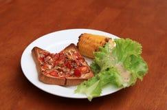 Autoguidez la pizza faite sur le pain coupé en tranches par place avec le maïs et la laitue grillés dans le plat rond blanc sur l image stock