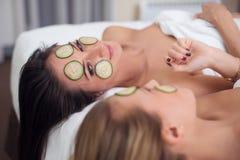 Autoguidez la station thermale Deux femmes tenant des morceaux de concombre sur leurs visages se trouvant le lit Photographie stock libre de droits