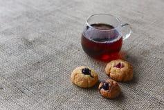 Autoguidez les biscuits cuits au four sur un tissu simple rugueux et une tasse de thé Images libres de droits