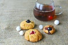 Autoguidez les biscuits cuits au four sur un tissu simple rugueux et une tasse de thé Photographie stock