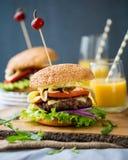Autoguidez les hamburgers faits avec de la laitue, le fromage et l'oignon caramélisé Photos stock