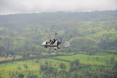 Autogyro flying above the tropical landscape royalty free stock photos