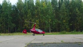 Autogyro Before Take-Off. Gyroplan on the runway before take-off with trees on the background stock footage