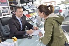 Autohändler, der dem Kunden Vertrag gibt stockfoto
