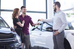 Autohändler, der einem glücklichen verheirateten Paar Autoschlüssel gibt stockbilder