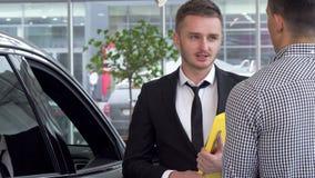 Autohändler, der Hände mit männlichem Kunden nach dem Verkauf eines Automobils rüttelt stock footage