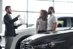 Autohandelaar die autosleutels tonen aan cliënten royalty-vrije stock foto's