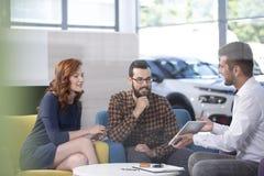 Autohandelaar die een aanbieding tonen aan zijn gelukkige cliënten in een autoshowro stock afbeeldingen