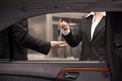 Autohandelaar die koperssleutels geven Stock Fotografie