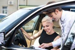 Autohandelaar en jonge vrouw die een contract ondertekenen Royalty-vrije Stock Afbeeldingen