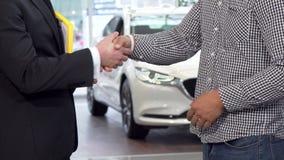 Autohandelaar het schudden handen met cliënt en het overgaan van autosleutels tot de man stock video