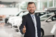 Autohandelaar in kostuum het stellen in autocentrum stock foto's