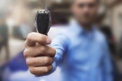 Autohaus- und Mietkonzepthintergrund Die Hand des Mannes stellt die Schlüssel dar lizenzfreie stockfotografie
