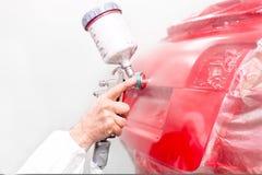 Autoingenieur die een rode verf op moderne auto in speciale cabine schilderen Stock Foto's