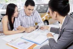 Autokäufer, welche die Regel lesen, um einen Autokredit zu kaufen Lizenzfreie Stockbilder