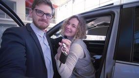 Autokaufen, lächelnde Familie mit Schlüsseln nehmen Bildtelefon auf Smartphone nahe neuem gekauftem Automobil im Selbstsalon stock video footage