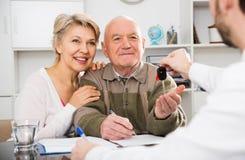 Autokaufvertrag des alten Mannes und der Frau unterzeichnender stockfotos