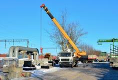 Autokraan lifling vrachtwagen met concrete plakken bij bouwwerfbouwvakker het navigeren met concrete langs opgeheven plak royalty-vrije stock foto
