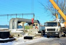 Autokraan lifling vrachtwagen met concrete plakken bij bouwwerfbouwvakker het navigeren met concrete langs opgeheven plak stock foto