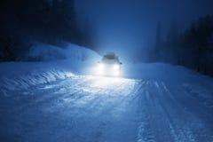 Autolichten in de winterbos Royalty-vrije Stock Afbeelding