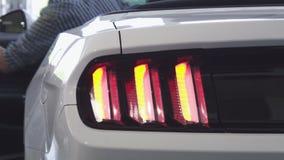 Autolichten die terwijl mens die in een auto krijgen opvlammen stock footage