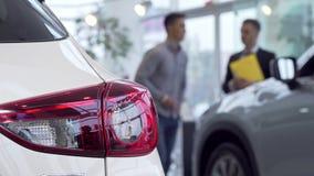 Autolichter auf dem Vordergrund, Mannkaufenauto an der Verkaufsstelle auf dem Hintergrund stock video footage